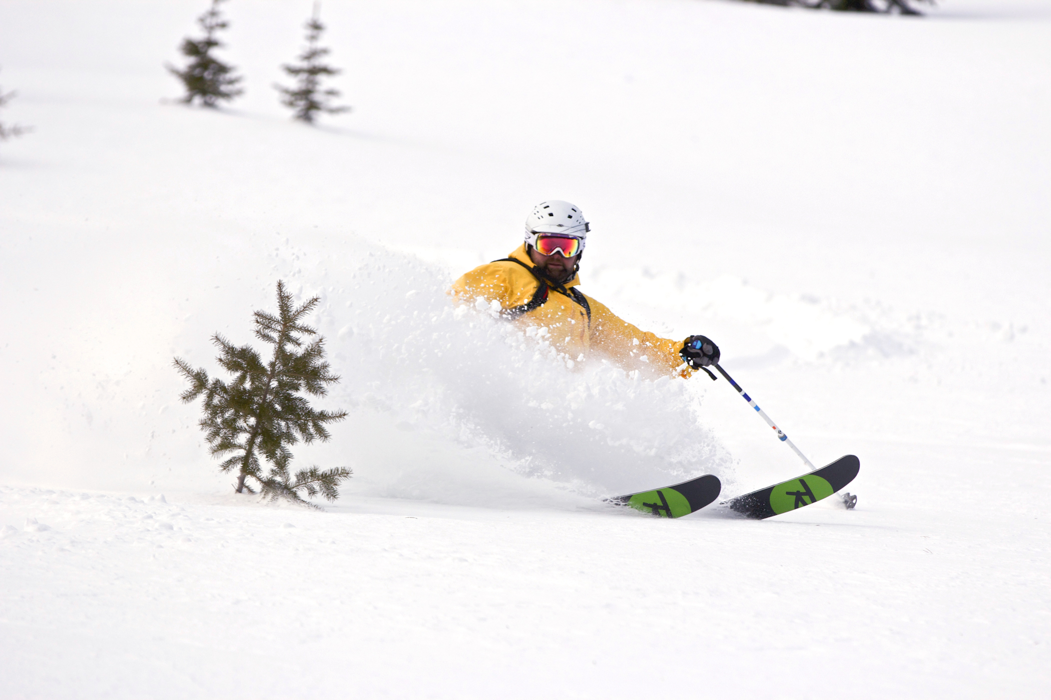A skier throws up a huge wall of snow at Castle Mountain Resort