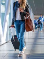 happy-woman-travelling-and-walking-in-airport-royalty-free-image-888767716-1538392950